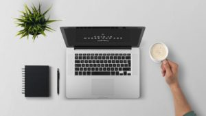 Notebook, kvet v kochlíku, káva, pero a notes položené na bielom stole. Pohľad zhora.