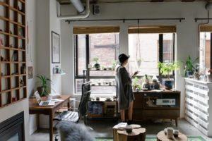 Žena v klobúku stojí pri okne vo svojom byte.